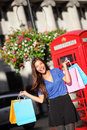 London shopping woman happy shopper with bags excited holding by red phone booth female smiling in england united Royalty Free Stock Image
