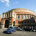 London taxi and royal albert hall uk may also called hackney carriage black cab in the background people cars present on Stock Image