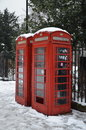 London telephone booths two stand on and under snow in in winter time Royalty Free Stock Photo