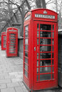 London telephone boots three red phone booths on the street Stock Image