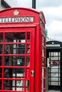 London telephone boxes two in the traditional red one and another black in the background Royalty Free Stock Images