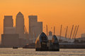 London thames barrier and canary wharf business district the river uk at sunset with orange sky Royalty Free Stock Image