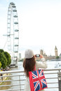 London tourist taking picture of river thames with eye big ben and palace westminster woman holding shopping bag Royalty Free Stock Photo