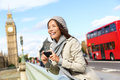 London tourist woman sightseeing taking pictures near big ben with red double decker bus holding smart phone camera smiling Royalty Free Stock Image