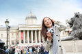 London tourist woman on trafalgar square in front of national gallery taking photo holding camera smiling happy laughing having Royalty Free Stock Photo
