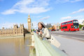 London travel woman tourist by big ben and red bus double decker girl taking photo on westminster bridge with smart phone camera Stock Image