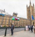 London / UK - June 26th 2019 - Pro-EU protester carries Wales and European Union flags outside Parliament in Westminster