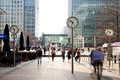 London uk march canary wharf square with clocks and office people walking by canary wharf place to work for more than people Royalty Free Stock Image