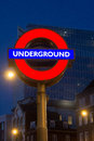 London underground sign at night illuminated with high rise building in background england Stock Images