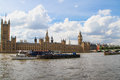 London united kingdom july barges are sailing by the parliament house and big ben on the thames river in Stock Photo