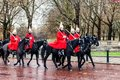 London, United Kingdom - 11/04/2016: Parade Royal Guard on black horses on street in London, after rain, in the background a bit b Royalty Free Stock Photo