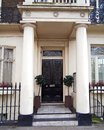 London, vintage house entrance with dark door and columns Royalty Free Stock Photo