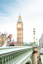 London woman happy by big ben laughing and drinking coffee in fall or winter young female professional on westminster bridge Royalty Free Stock Photos