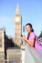 London woman runner listening to music by big ben on smartphone near female running girl resting after training in city fitness Stock Photo