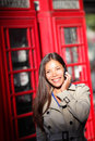 London woman on smartphone by red phone booth taking young casual female business having conversation mobile smart Royalty Free Stock Photography