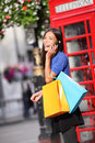 London woman talking happy smart phone shopping on while laughing on mobile holding bags by red booth female Stock Photos