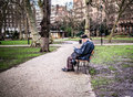 Londoner sits on bench reading in russell square side view of man with long gray hair cap seated park bloomsbury london during Royalty Free Stock Photography