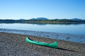 Lone canoe on shore an old resting the pebbled the coast of maine Royalty Free Stock Images