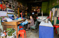 Lone elderly lady sewing clothes in a garage full of different things Royalty Free Stock Photo