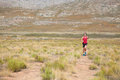 Lone female athlete running on a trail in the mountains Stock Photos