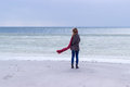 Lone sad beautiful girl walking along the shore of the frozen sea on a cold day rubella chicken with a red scarf on the neck Royalty Free Stock Photos