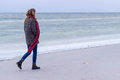 Lone sad beautiful girl walking along the shore of the frozen sea on a cold day rubella chicken with a red scarf on the neck Royalty Free Stock Image