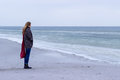 Lone sad beautiful girl walking along the shore of the frozen sea on a cold day rubella chicken with a red scarf on the neck Royalty Free Stock Photo