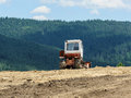 Lone tractor in mountain forest in background green pines Royalty Free Stock Photos