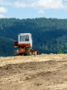 Lone tractor in mountain forest in background scene Royalty Free Stock Image