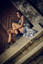 Loneliness beautiful young woman sitting on a stair and holding cigar and sunglasses Royalty Free Stock Photo