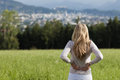 Loneliness a blond woman stands with her back to the camera in a green field overlooking a distant town in the valley in a Stock Images