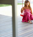Loneliness: A cute girl sitting on a swing Royalty Free Stock Image