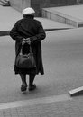 Loneliness lonely elderly woman walking down the street backside view baku city azerbaijan Royalty Free Stock Image