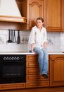Loneliness lonely girl sitting on the kitchen table Royalty Free Stock Image