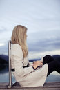 Loneliness a lonely young woman sits on a wooden deck overlooking a mountain lake staring across the water close up side view as Royalty Free Stock Photo