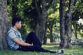 Loneliness moment asian man sitting against a tree in the park and vintage tone Royalty Free Stock Photos