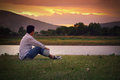 Loneliness moment asian man sitting on the grass in sunset Stock Photos