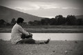 Loneliness moment asian man sitting on the grass in sunset black and white tone Royalty Free Stock Photos