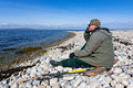 Lonely angler enjoy beautiful swedish sea coast landscape Stock Photo