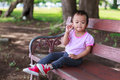 Lonely asian baby girl sitting on bench wooden in park Royalty Free Stock Images