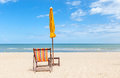 Lonely beach chair and sun umbrella on beautiful beach. Royalty Free Stock Photo