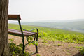 Lonely bench near tree with hills distant in the front Royalty Free Stock Photos