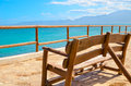 Lonely bench on a viewing platform with views of the sea and the mountains back view Royalty Free Stock Image