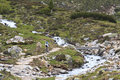 Lonely biker in tyroler ziller valley austria biking along and over the zamser bach a mountain stream the zillertal alps this Stock Image