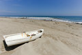 A lonely boat sits on the sand on beach in mancora peru Royalty Free Stock Photography