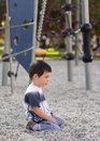 Lonely bored child sitting on ground in playground Royalty Free Stock Photography