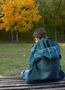 Lonely boy is sitting on a bench Royalty Free Stock Photography