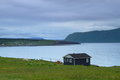 Lonely cabin wooden on the shore in nordic landscape Stock Image