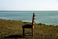 Lonely chair at water a scene with a single the with shade and sun Royalty Free Stock Photography
