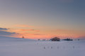 Lonely chalet on snowy meadow at winter sunset Royalty Free Stock Photo